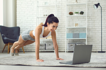 Online home sports. Young fit woman exercising to video tutorial indoors, doing plank or push up exercise