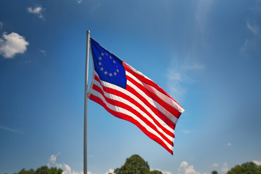 A copy of the Betsy Ross American flag with 13 stars flying against a blue sky.