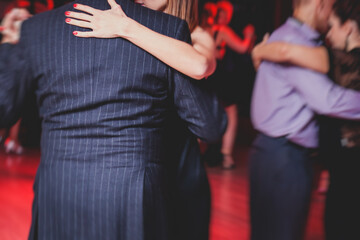 Couples dancing argentinian dance milonga in the ballroom, tango lesson in the red lights, dance festival