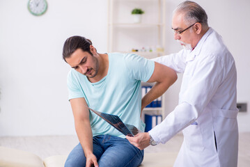 Young back injured man visiting experienced male doctor