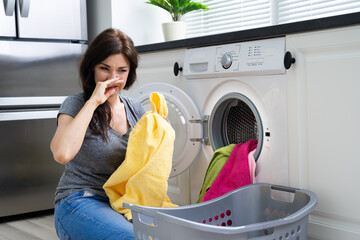 Woman Looking At Smelly Clothes Out Of Washing Machine