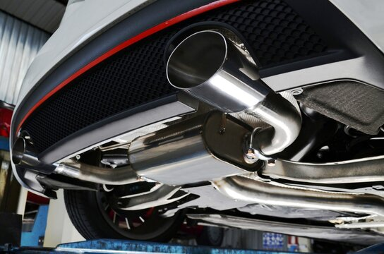 New generation of sportive mufflers. Oval or round Car Exhaust Tailpipe chromed made of stainless steel on powerful sport car bumper. Close up