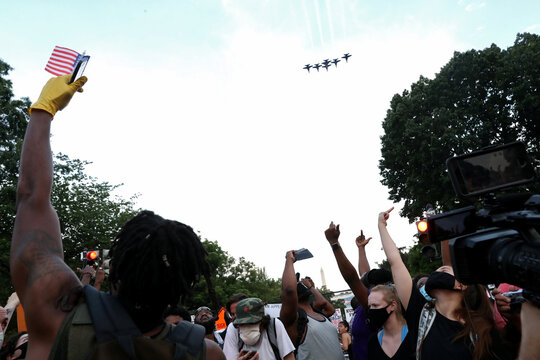 Protesters against racial inequality and police violence gesture near Black Lives Matter Plaza, as military aircraft perform a flypast during Fourth of July holiday, in Washington