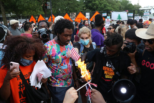 A group of protesters burn American flags and leaflets with the flag, even as other protesters disagreed with the act, during a protest against racial inequality and police violence near Black Lives Matter Plaza