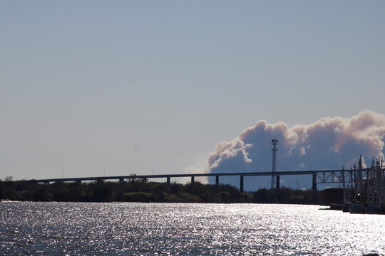 smoke from a factory, sky, industry, factory, water, bridge, sea, power, industrial, smoke, blue, pollution, winter, landscape, travel, plant, city, clouds, snow, river, building, pier, sun, tower,