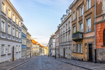 Tuinposter Smal steegje Warsaw, Poland old town historic cobblestone road street empty narrow alley during sunny sunset sunrise winter day morning
