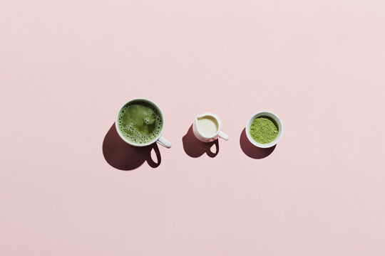 Vegan matcha latte with oat milk and ingredients on pink