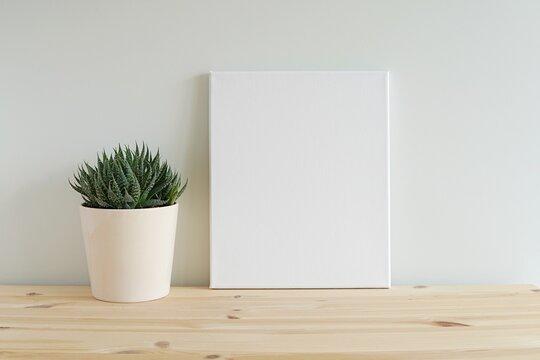 Blank canvas frame mockup on wooden shelf, cactus plant, empty frame mock-up for artwork, photo, painting, minimal interior.