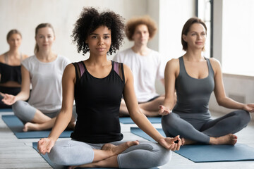 Peaceful young african american healthy woman sitting in lotus position with open hips and mudra gesture folded fingers, relaxing after intensive group yoga class in modern studio with diverse people.