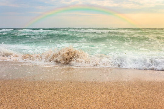 storm on the sandy beach at sunset. dramatic ocean scenery with cloudy sky. rainbow above the rough water and crashing waves in evening light