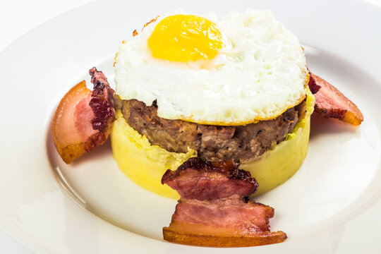 mom made  breakfast. fried egg and meat patty on top of smashed potato, decorated with bacon. food isolated on the white background. close up view