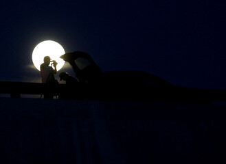 People are seen taking pictures during the full moon in Monterrey