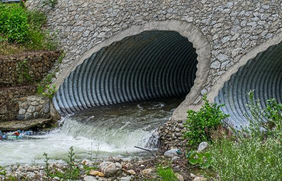 Water drains through pipes, under a bridge.
