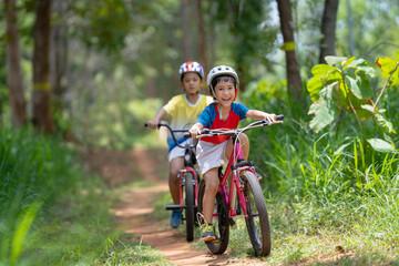 Asian children are happy mountain biking.
