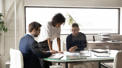 Diverse multiethnic businesspeople brainstorm discuss company financial paperwork at boardroom meeting together, multiracial colleagues talk consider paper documents at team briefing in office