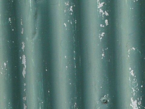 Galvanized corrugated metal wall background with chipped green paint