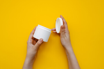 Human hands opening a white blank body cream jar on clean yellow background.