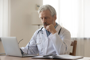 Pensive mature male doctor or GP sit at desk in hospital look at laptop screen thinking of patient diagnosis, thoughtful old man physician or therapist work on computer in cabinet, make decision