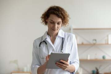 Young Caucasian female doctor or GP in white medical uniform use consult patient on tablet gadget, woman nurse or physician work on modern pad device, fill anamnesis, modern clinic hospital concept