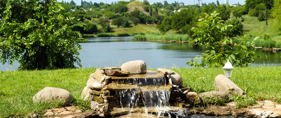 Home waterfall. Stones on the background of a reservoir. Waterfall with your own hands. Wall mural