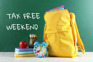 Backpack with school stationery and text TAX FREE WEEKEND written on chalkboard in classroom