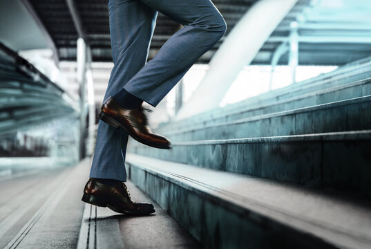 Motivation and challenging Concept. Steps Forward into a Success. Low Section of Businessman Walking Up on Staircase