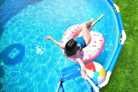 Pool time. Girl has fun in a summer metal frame pool.