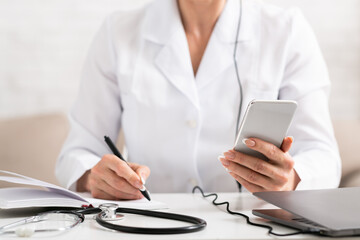 Doctor work remotely online. Woman doctor in white coat makes notes in notebook