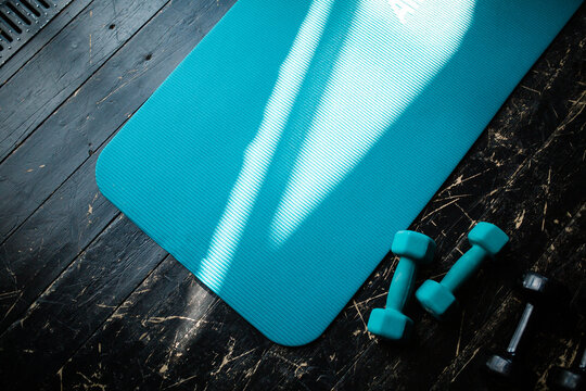 Top view on sports equipment. Blue dumbbells and a yoga mat for warming up before doing sports