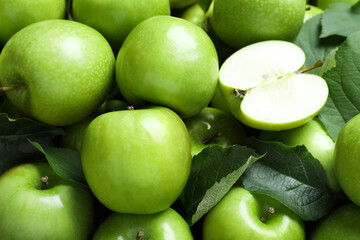 Fototapete - Pile of tasty green apples with leaves as background, closeup