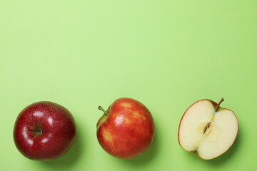 Fototapete - Tasty red apples on green background, flat lay. Space for text