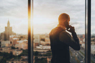 Silhouette of caucasian man entrepreneur having a phone conversation while standing next to a panoramic window of a skyscraper with cityscape and highway, a copy space area on the left for an ad text
