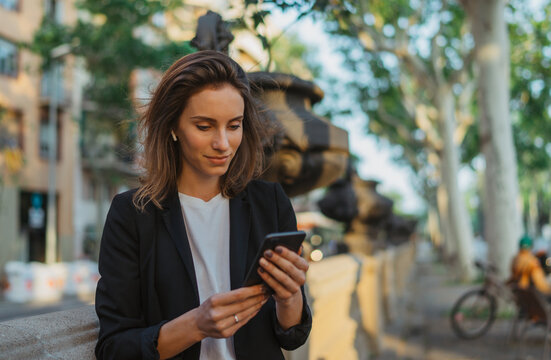 focus on businesswoman in suit calling on cell phone in park, portrait elegant woman with smartphone and wireless earphones on sun day in street city, female manager using mobile phone outdoors