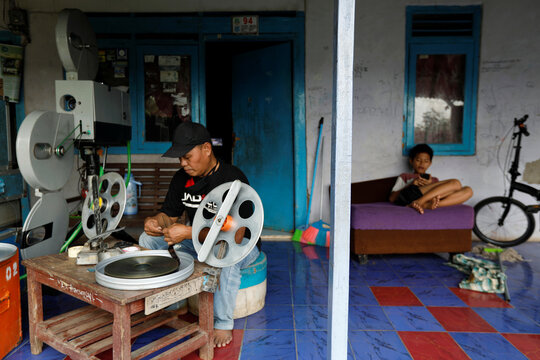 Nur Iyan, a 48-year-old film collector, prepares celluloid of a movie which will be screened in a 'mobile cinema', following the coronavirus disease (COVID-19) outbreak, at his house in South Tangerang, on the outskirts of Jakarta