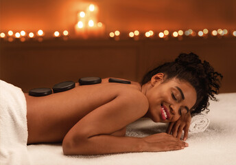 Relaxed african girl enjoying hot stones massage at spa