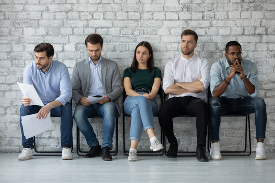 Five multi racial young people applicants sitting in line on chairs in office corridor feels nervous unsure job interview success, highly competitive job market, tension rises due to waiting concept