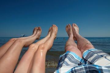 Sunbathing family on the beach, only legs.