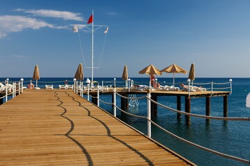 Wooden pier with sunbathing people on the beach.