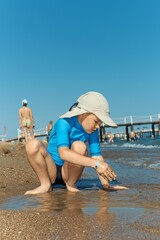 Little boy enjoying summer, playing on the beach.