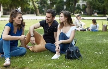 Young friends sitting in park on the grass, talking at springtime.