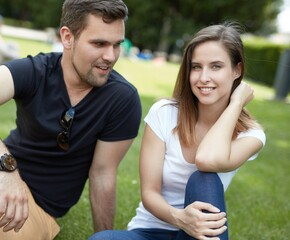 Attractive young loving couple sitting in park on the grass, smiling.