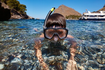 Snorkeling boy at summertime in the sea.
