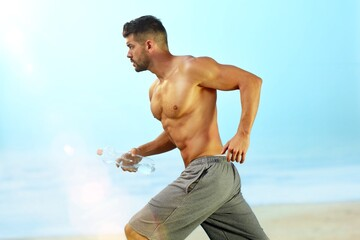 Athletic young man running on the beach at summertime.