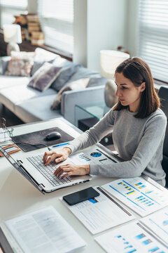 Focused woman working from home office on laptop