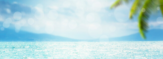 Blurred summer natural marine tropical blue background with palm leaves and sunbeams of light. Sea and sky with white clouds. Panoramic banner with copy space