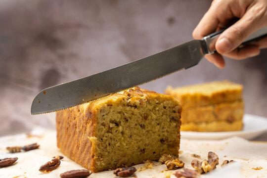 Hand with knife ready to slice a piece of banana walnut pound cake