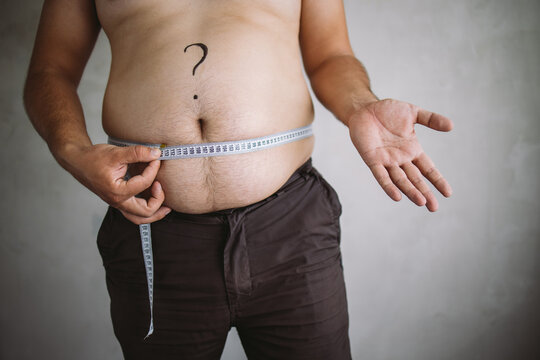 Overweight man measuring waist with measure tape, close up image. Weight loss, motivation, fat burning