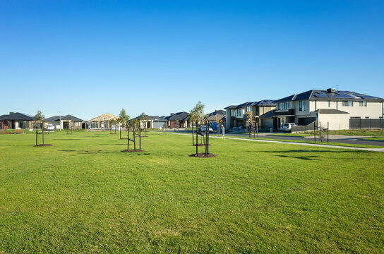 A public park with green lawn/grass and young trees surrounded by new residential houses/Australian homes in a Melbourne's suburb. Tarneit, VIC Australia. Background texture of a. suburban park.