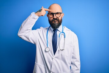 Handsome bald doctor man with beard wearing glasses and stethoscope over blue background pointing...