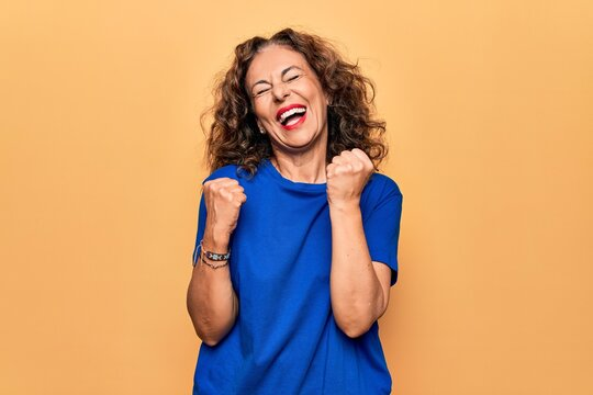 Middle age beautiful woman wearing casual t-shirt standing over isolated yellow background celebrating surprised and amazed for success with arms raised and eyes closed